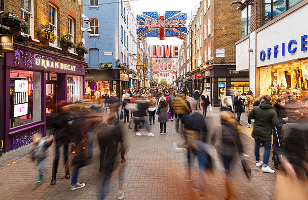 Motion blur of Christmas shoppers on Carnaby Street, London. London, England - December 17, 2016: Motion blur of Christmas shoppers on Carnaby Street, London. In London, England. On 17th December 2016. carnaby street stock pictures, royalty-free photos & images