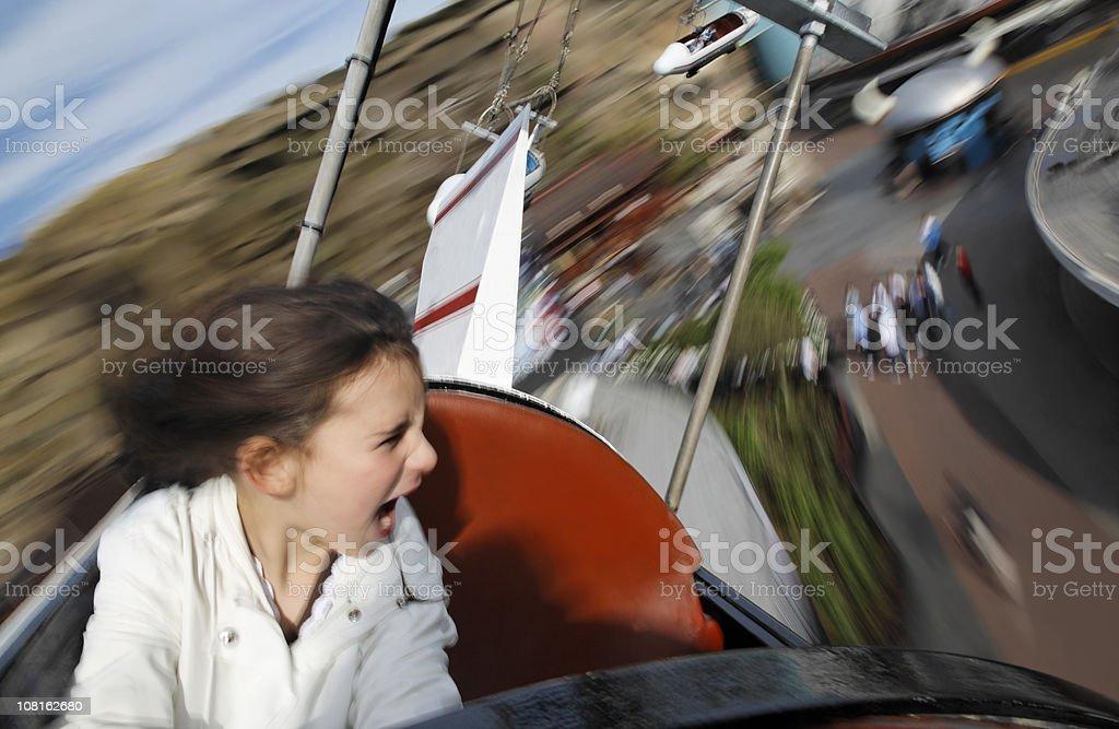Motion Blur of Little Girl Riding Amusement Park Ride stock photo