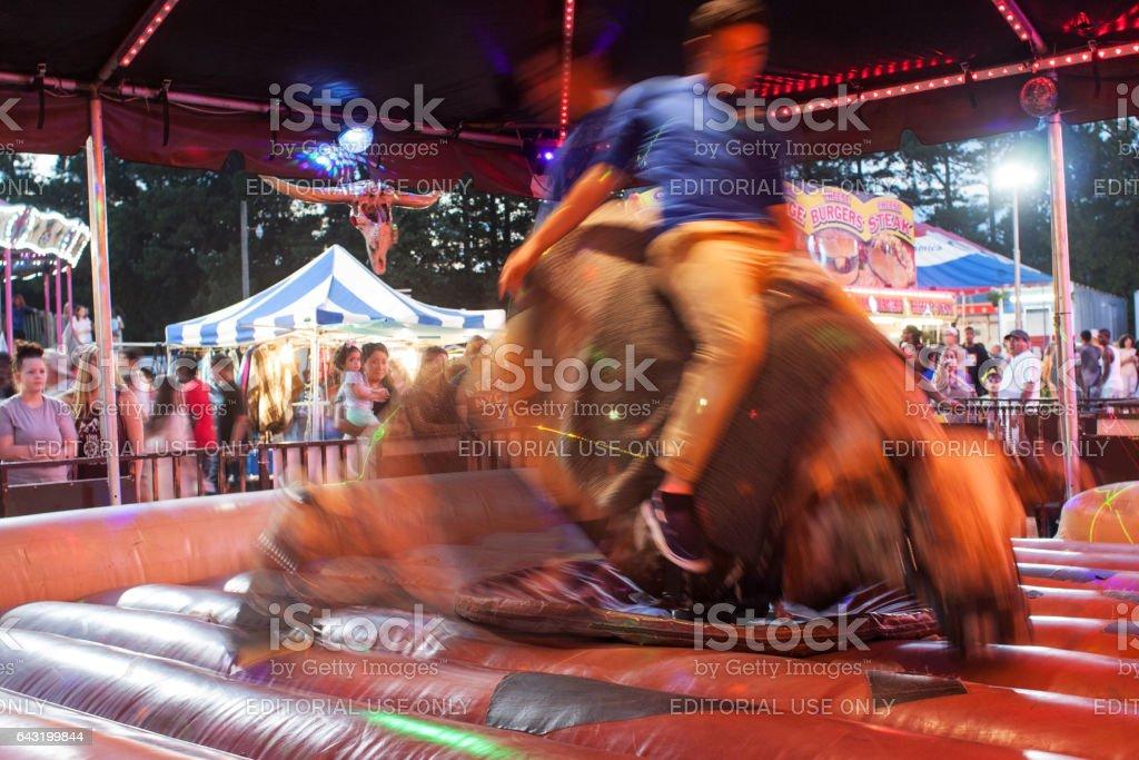 Motion Blur Of Man Riding Mechanical Bull At County Fair - Photo