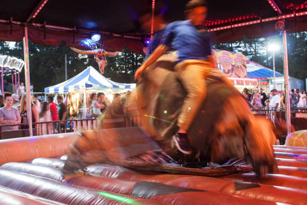 motion blur of man riding mechanical bull at county fair - rodeo photos et images de collection
