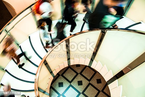 180698194 istock photo Motion Blur of People on Abstract Spiral Staircase 1061338538