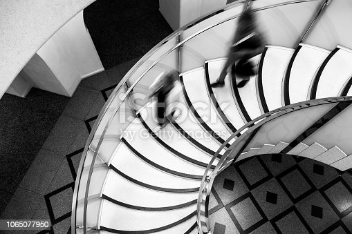 180698194 istock photo Motion Blur of People on Abstract Spiral Staircase 1065077950
