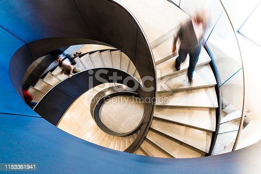 180698194 istock photo Motion Blur of People on Abstract Spiral Staircase 1153361941