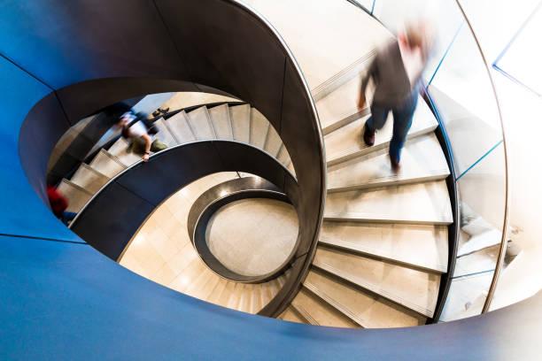 bewegtströde von menschen auf abstrak-staircase - bogen architektonisches detail stock-fotos und bilder