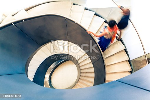 Overhead view depicting blurred motion of people walking up and down a spiral staircase. The people are completely blurred, and the slow shutter speed makes it appear as though the people are moving fast. Image taken at City Hall in London, which is a publicly owned building that is accessible to the general public without any photographic restrictions. Room for copy space.