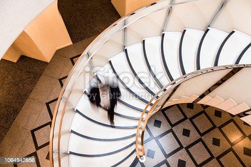 684803840istockphoto Motion Blur of Speeding Businessman on Abstract Spiral Staircase 1064942656
