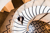 Overhead view depicting blurred motion of a business person (we cannot tell if it is a man or a woman) walking down a spiral staircase. The person is completely blurred, and the slow shutter speed makes it appear as though he is moving fast. Horizontal color image with room for copy space. Image taken at City Hall in London, which is a publicly owned building that is accessible to the general public without any photographic restrictions.