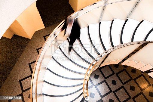 684803840istockphoto Motion Blur of Speeding Businessman on Abstract Spiral Staircase 1064945508