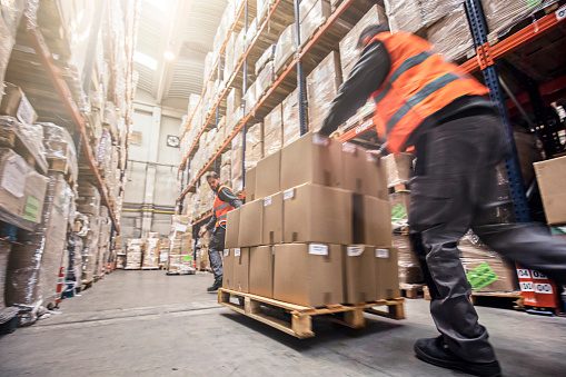 Motion blur of two men moving boxes in a warehouse.