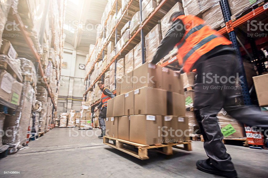 Motion blur of two men moving boxes in a warehouse - foto de stock