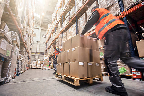 motion blur of two men moving boxes in a warehouse - logistica foto e immagini stock
