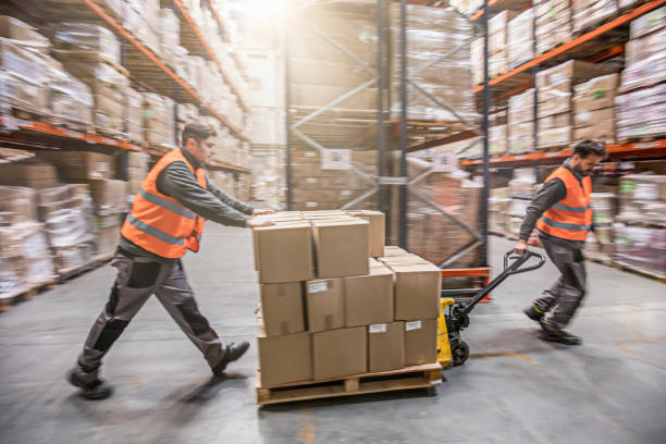 Motion blur of two men moving boxes in a warehouse - Photo