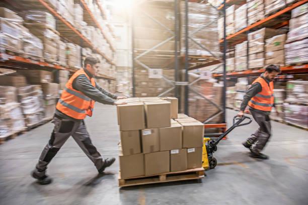 motion blur of two men moving boxes in a warehouse - umzug transport stock-fotos und bilder