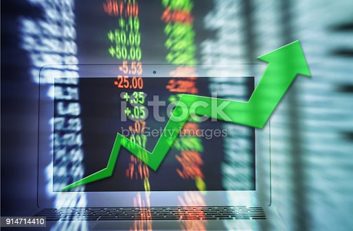 istock Motion blur of up trend arrow line chart with computer notebook for trade on blurred stock board background in business concept 914714410