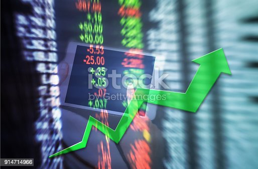istock Motion blur of up trend arrow line chart with tablet for trade on blurred stock board background in business concept 914714966