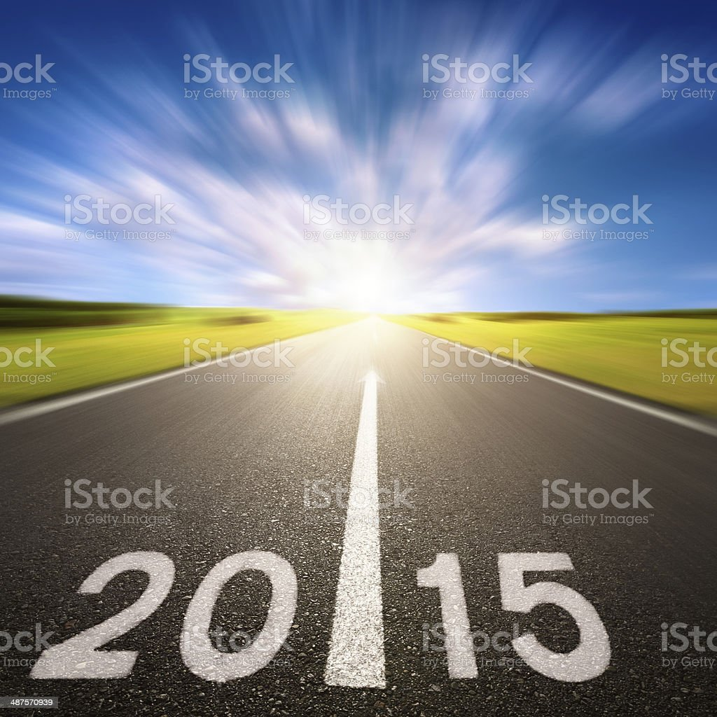 Motion blurred asphalt road forward to 2015 stock photo