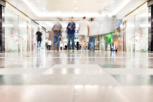 Motion blurred customers walking in shopping mall, Hong Kong stock photo