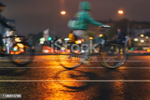 929609038istockphoto Motion blurred image of riding bikes. Silhouettes of abstract unrecognizable people, night city, illumination bokeh. Modern active healthy lifestyle, sport 1186913769