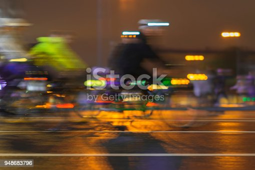 929609038istockphoto Motion blurred image of riding cyclists. Parade of bicyclists in city, night, abstract. Modern active lifestyle, healthy lifestyle concept 948683796