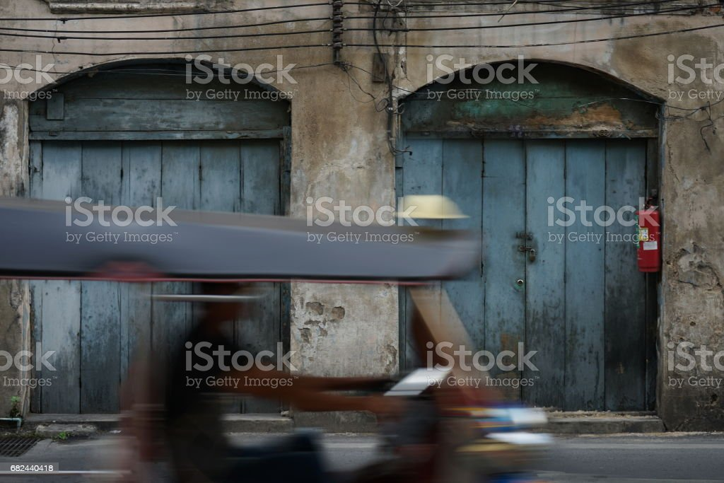 Motion blurred image of Tuk Tuk bike in Bangkok with Old town building in the background royalty-free stock photo