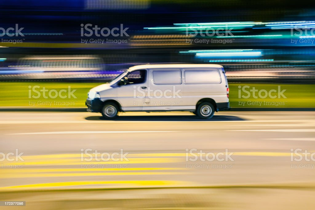 Motion blurred image of van going fast through city street royalty-free stock photo