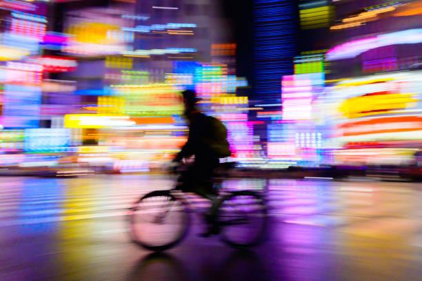 Bewegung verschwommen von Fahrer fahren Fahrrad mit neonhellem Hintergrund – Foto