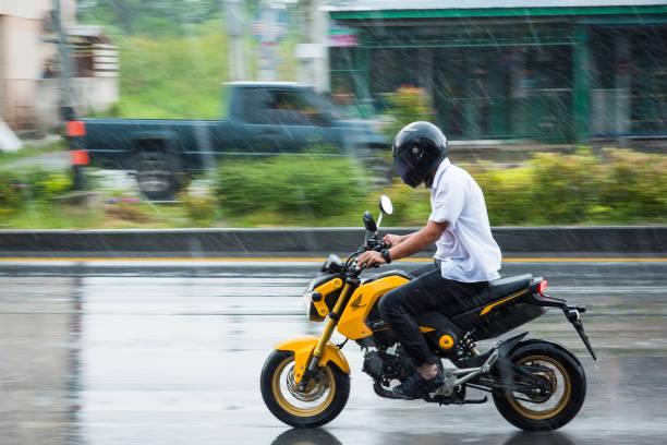 Bewegung unscharfen Foto von unbekannten Namen Personen Motorrad im Regen unterwegs in Nonthaburi, Thailand schwenken. – Foto
