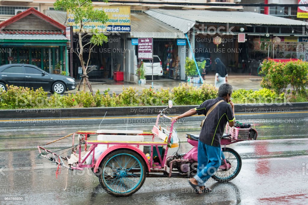 Motion Blurred panning photo of Unidentified name people riding tricycle in the rain on road at Nonthaburi, Thailand. royalty-free stock photo