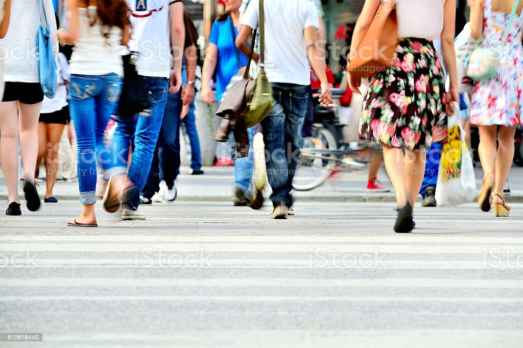 Motion blurred pedestrians crossing sunlit street stock photo