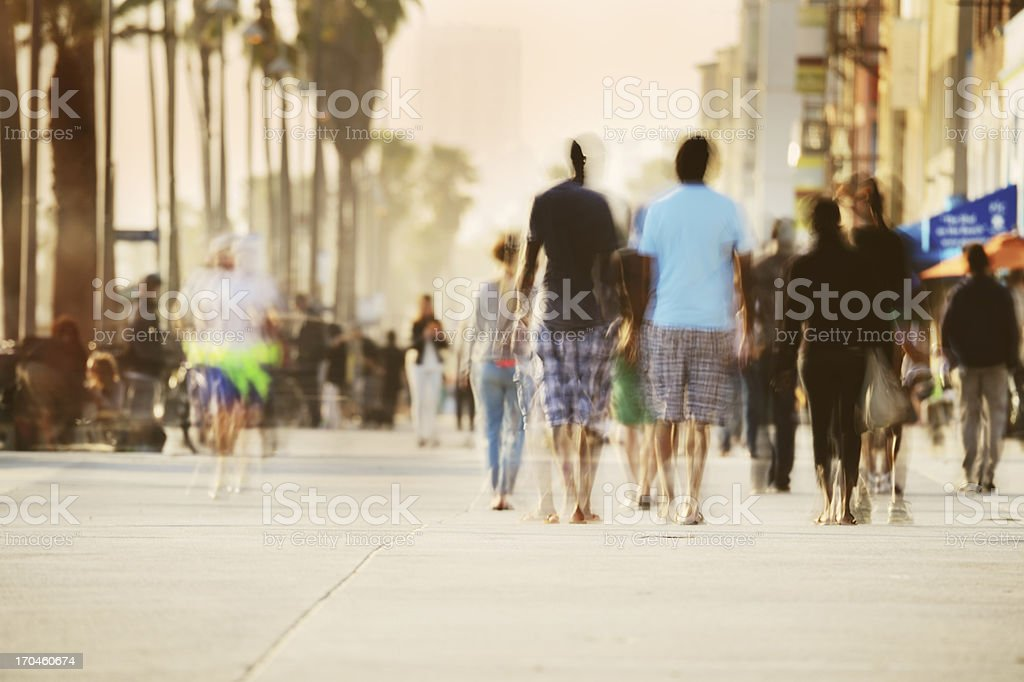 Motion blurred pedestrians on boardwalk stock photo