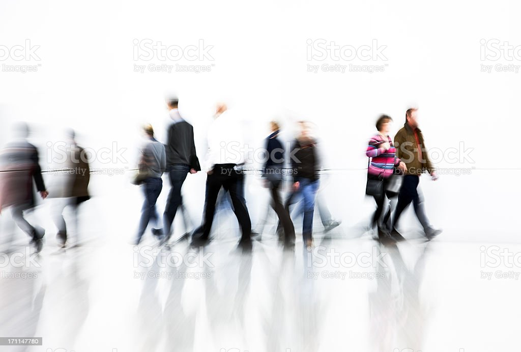Motion Blurred Pedestrians Rushing In Front Of White Wall royalty-free stock photo