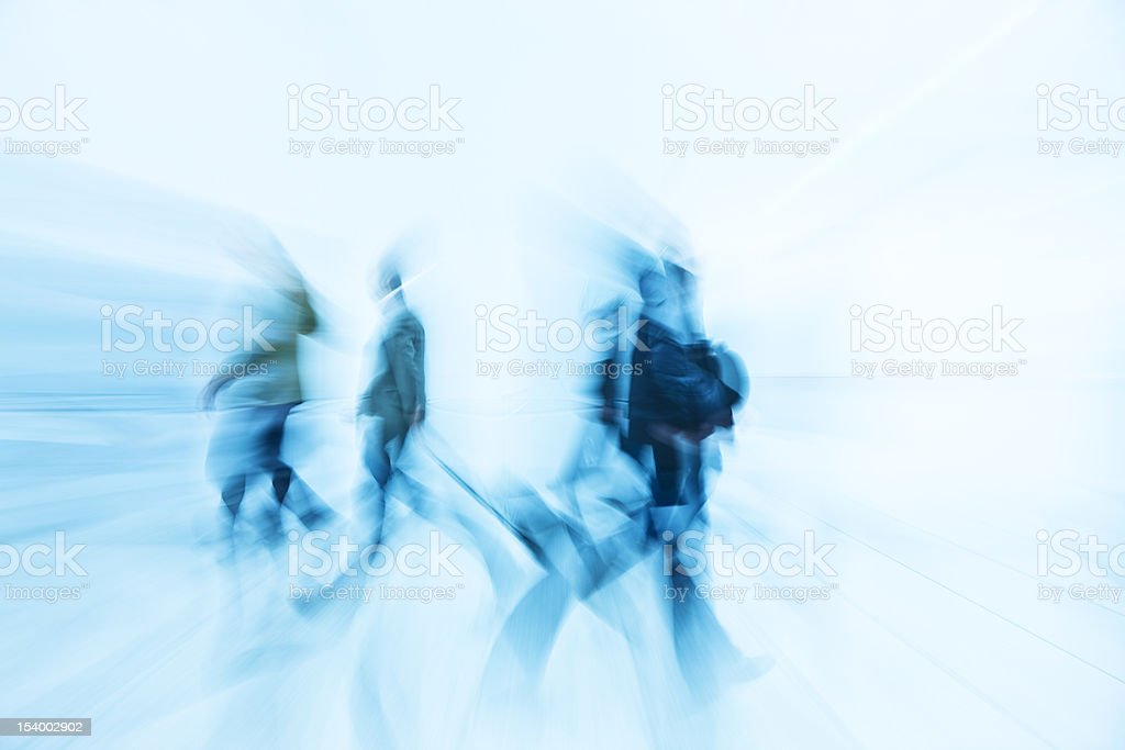Motion Blurred Pedestrians Walking in White Hallway royalty-free stock photo