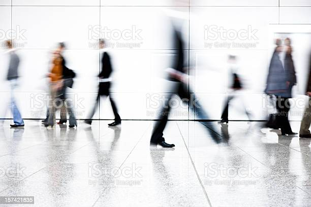 Motion Blurred People Walking Down Corridor Stock Photo - Download Image Now