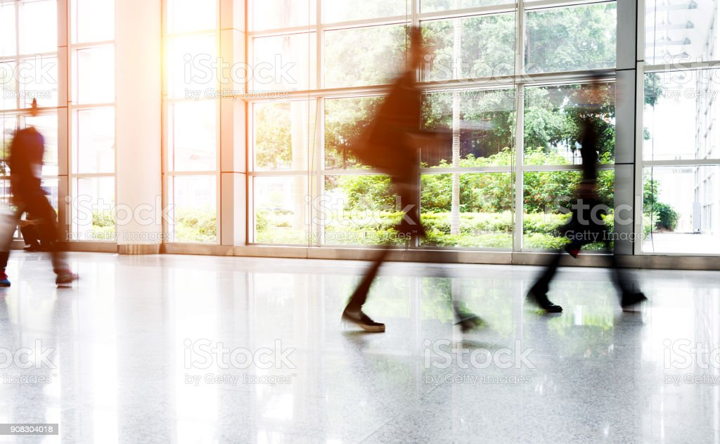 Motion blurred people walking in modern office stock photo