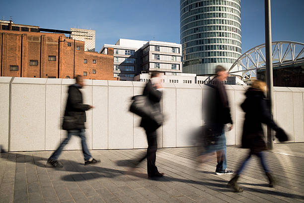 Motion blurred people walking on a city pavement. stock photo