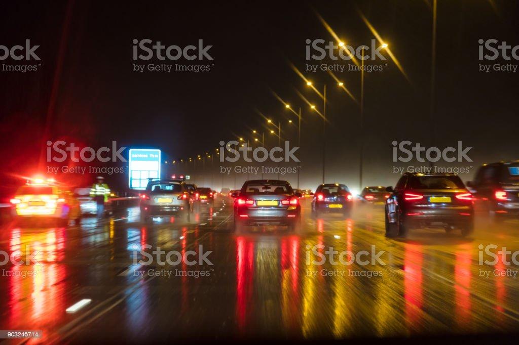 Movimiento borrosa fotografía del tráfico en la noche bajo la lluvia en una autopista británica con el oficial de policía y coche - foto de stock