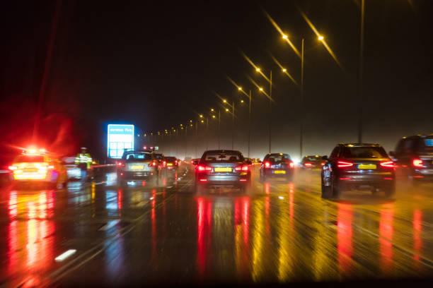 Motion blurred photograph of traffic at in night in the rain on a British motorway with police officer and car Motion blurred photograph of traffic at in night in the rain on a British motorway with police officer and car multiple lane highway stock pictures, royalty-free photos & images