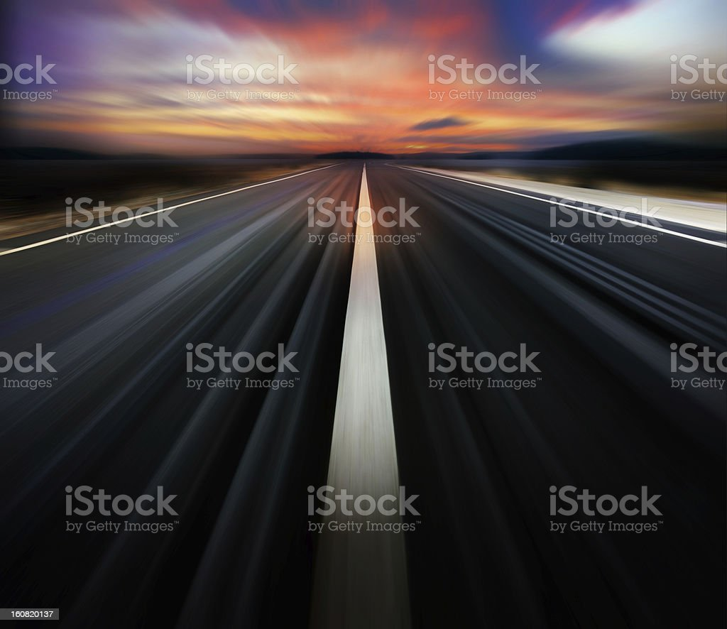 Motion blurred road and dramatic sky Dark road, white line, dramatic sky. New asphalt road and a single white line dividing the lanes. Absence Stock Photo