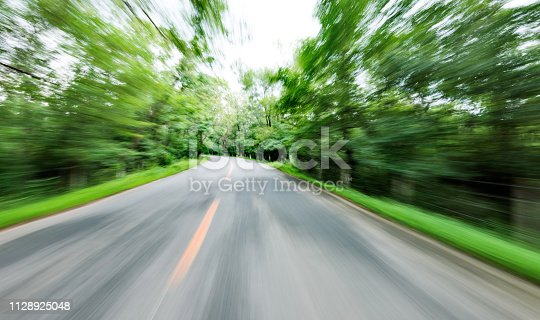 Motion blurred road in green forest