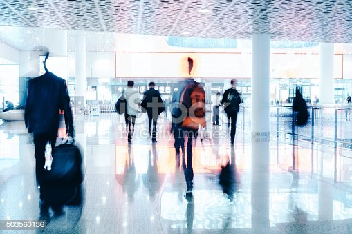 istock motion blurred travellers walking in modern airport hallway 503560136