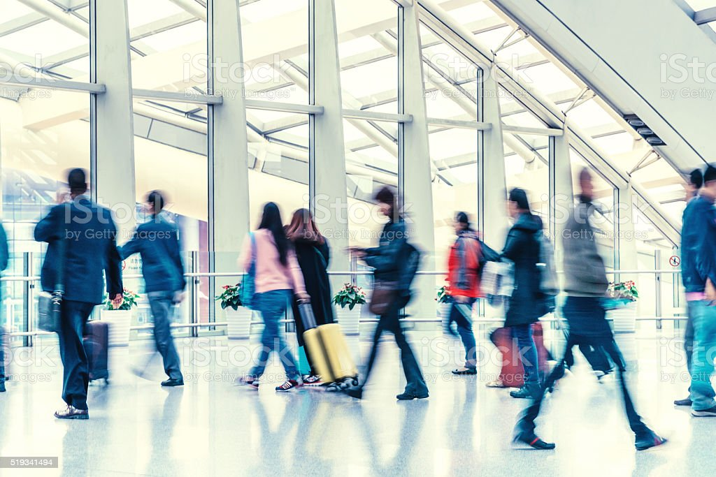 motion blurred travellers walking in modern hallway stock photo