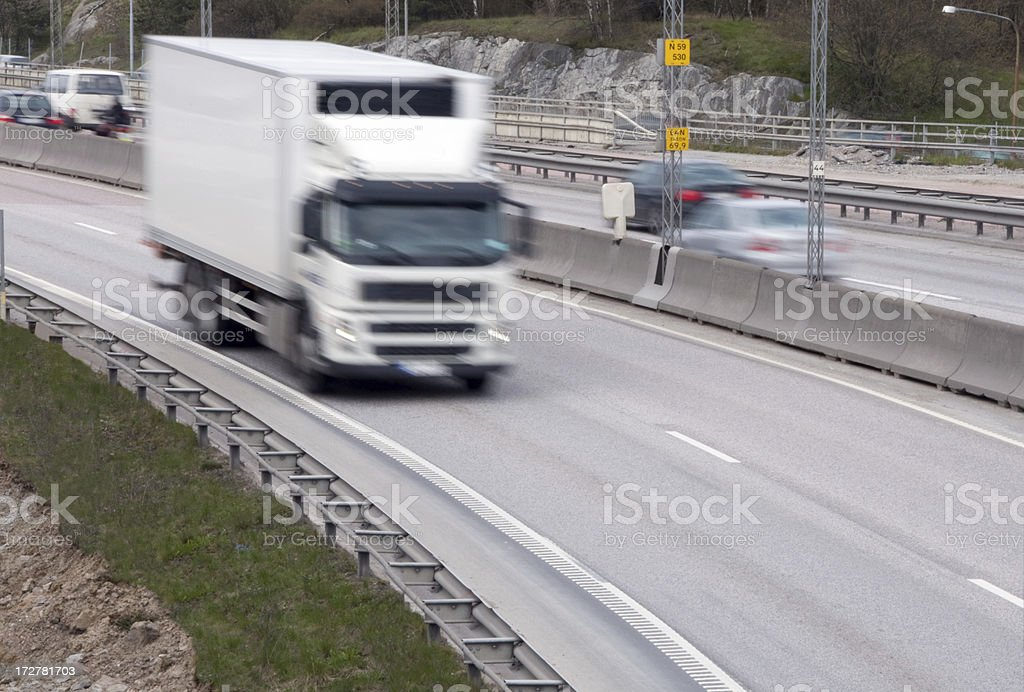 Motion blurred white truck on two lane highway stock photo