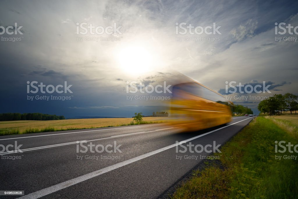 Motion blurred yellow bus traveling on the asphalt road in the countryside under the sun shining through dramatic clouds before the storm stock photo