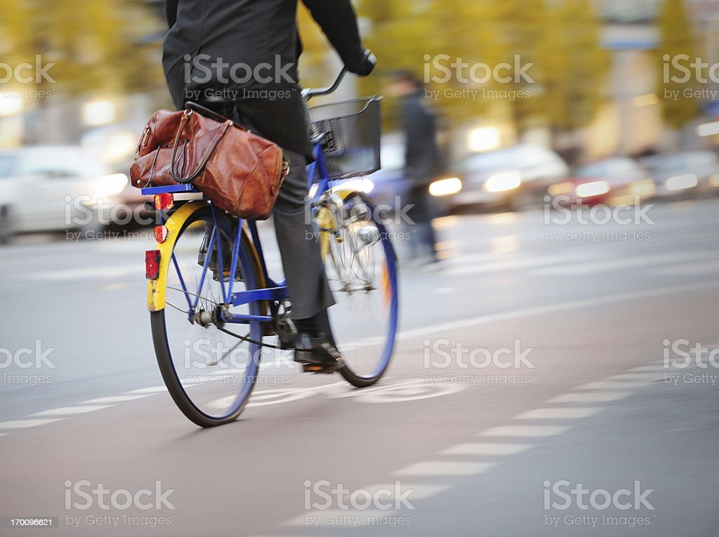 Motion blurred young adult businessman in bike lane and traffic stock photo