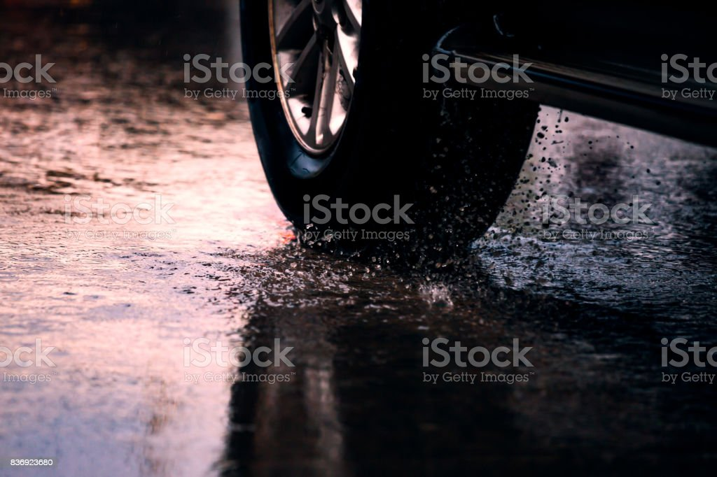 Motion car in rain big puddle with water splashing from the wheels stock photo