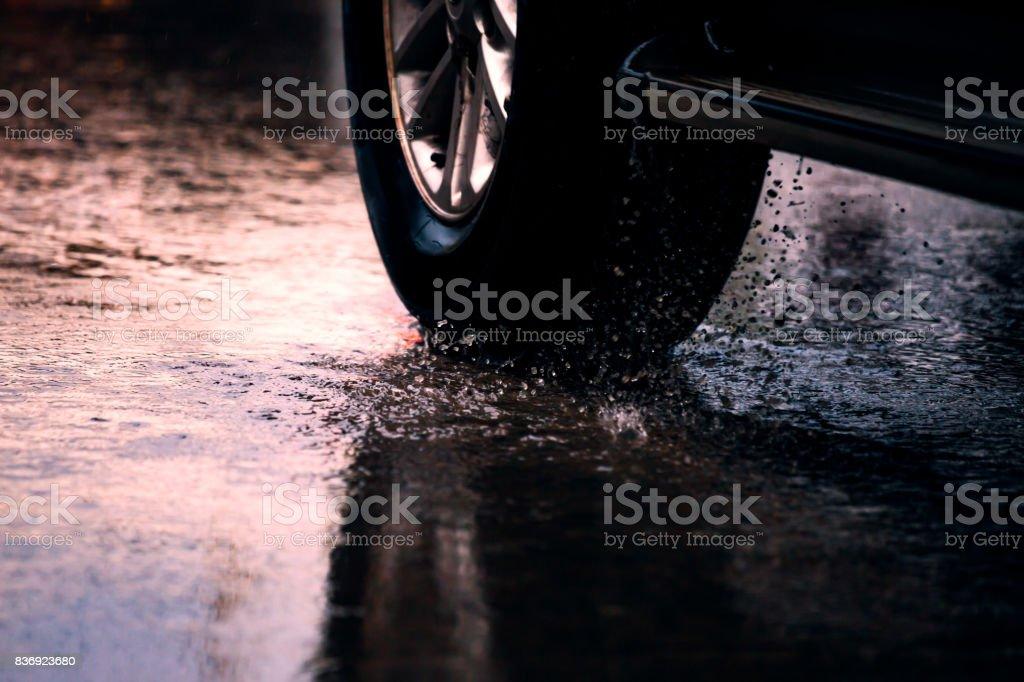 Coche de movimiento en charco de lluvia con agua que salpica de las ruedas - foto de stock