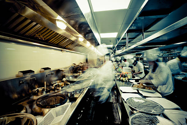 motion chefs  of a restaurant kitchen - busy restaurant kitchen stock pictures, royalty-free photos & images