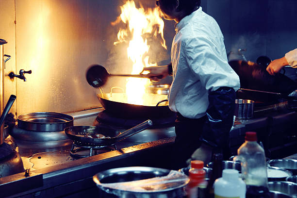 motion chefs of a restaurant kitchen motion chefs of a restaurant kitchen chef's whites stock pictures, royalty-free photos & images