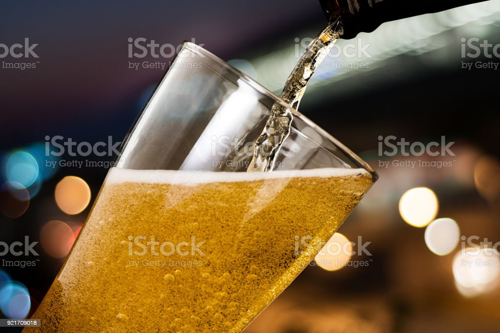 Motion of beer pouring from bottle into glass on bokeh light night background stock photo