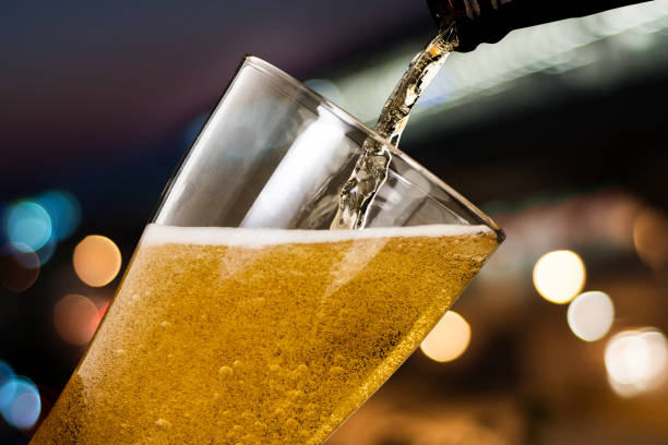 Motion of beer pouring from bottle into glass on bokeh light night background Motion of beer pouring from bottle into glass on bokeh light night background beer glass stock pictures, royalty-free photos & images